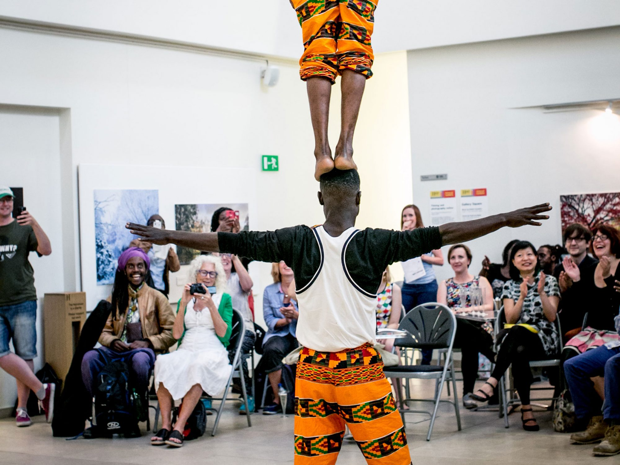 One performer stands on a second performers head in a large white airy room. They are being watched by an audience on a balcony and on their level.