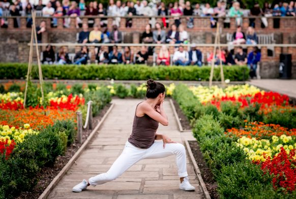 A dancer is performing on a garden path between some flower bed with red and yellow flowers. A group of people at watching at the far end of the garden.