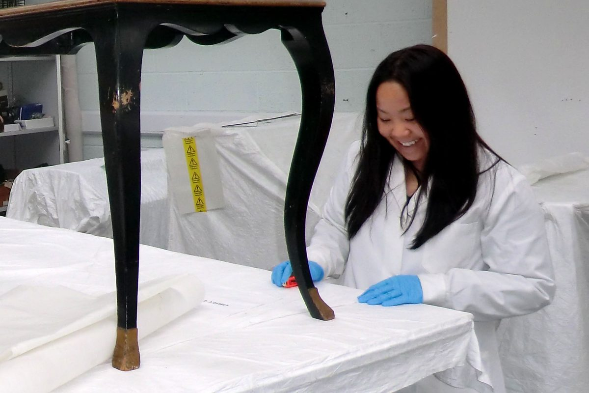 A woman in a white coat and blue gloves is looking at the wooden legs of an instrument stool
