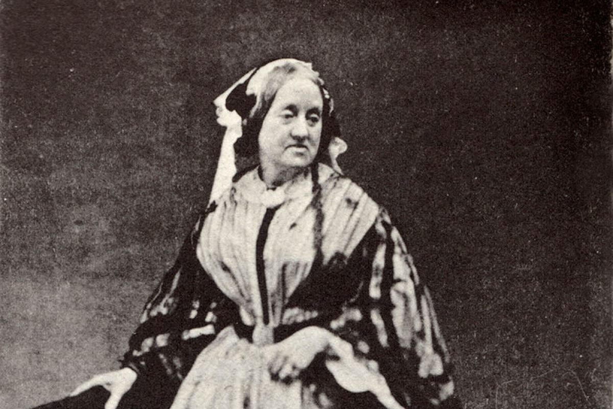 A black and white portrait of a woman in a full Victorian outfit