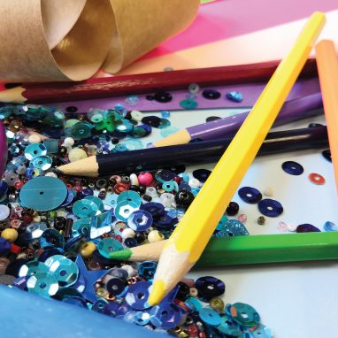 a close up of assorted arts and crafts materials like scissors, pens, sequins and tape