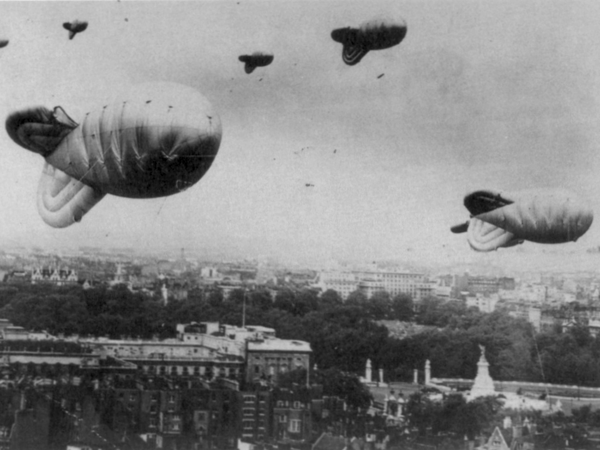 A black and white picture of large balloons over London in the sky