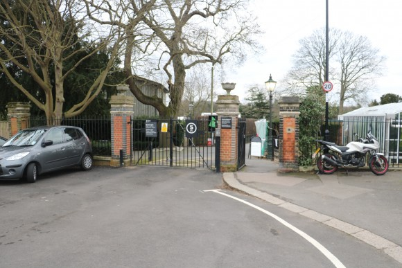 An old fashioned looking metal gate with brick supports to either side. There is a grey car parked next to them on the left and a motorbike parked to the right. A pedestian gate is open to the right hand side. The gates themselves are closed and a sign saying 5 miles per hour is just visible.