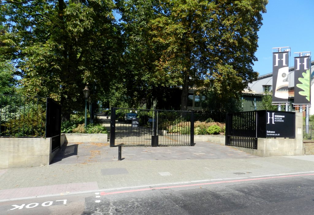 A picture taken from a road towards some black gates, which have two open sections to either side and a central closed panel. A sign to the right says Horniman Museum and Gardens entrance horniman.ac.uk. There are gree trees and a path leading lighly upward in a straight line. There is an old fashion lamp just inside the gates, and some low buildings to the right