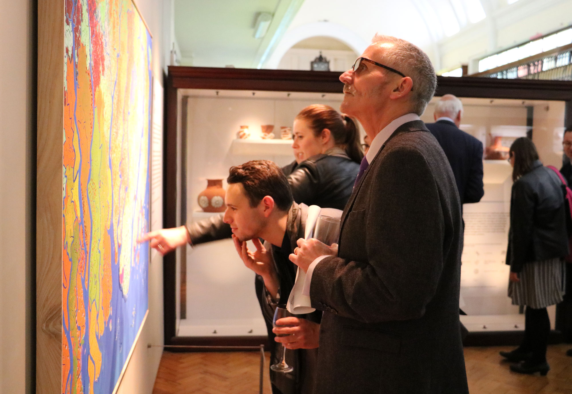 A group of adults are looking at artwork on a wall inside a gallery