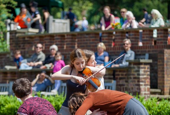 Dancers and a violinist perform in a garden with an audience watching from a seated area behind the performers.