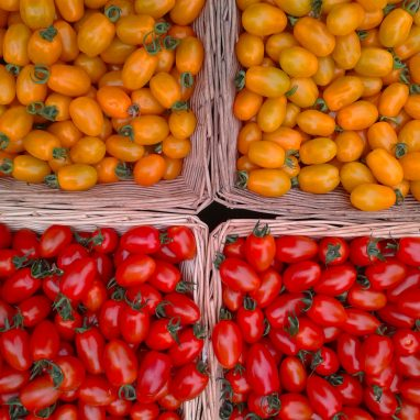 Four baskets with yellow baby tomatoes in the top two and red baby tomatoes in the bottom one