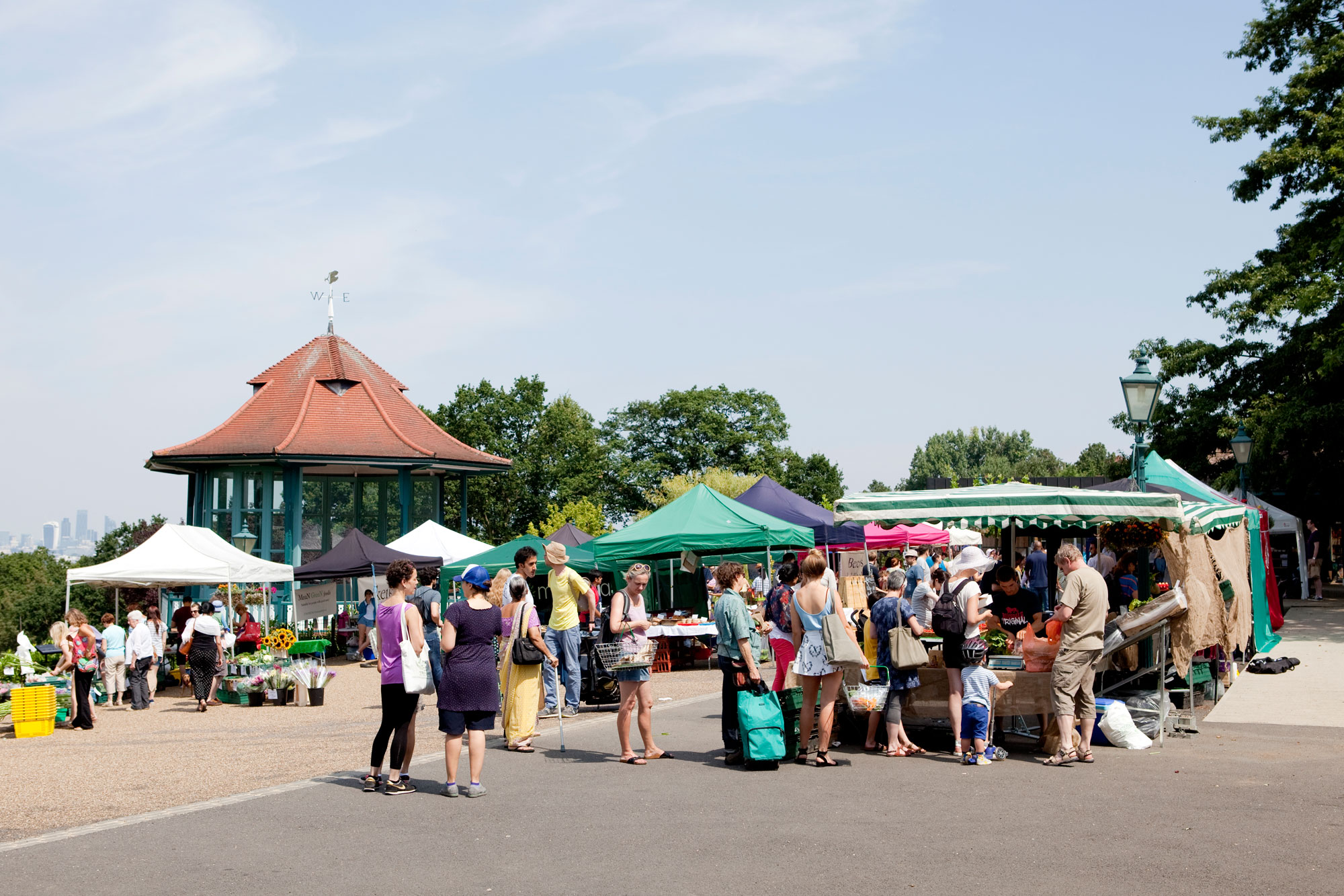 A group of stalls in a terrace outdoors next to a bandstand. There are people queuing at the stalls and the day is sunny and blue