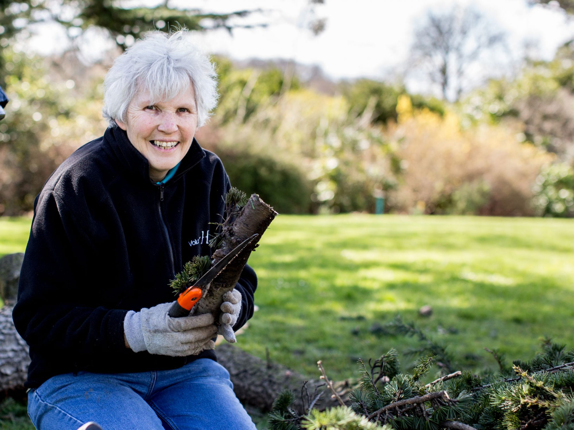 A volunteer woman in the Gardens, kneeling down and holding a log. Someone else is just seen bending over next to her. She is smiling at the camera