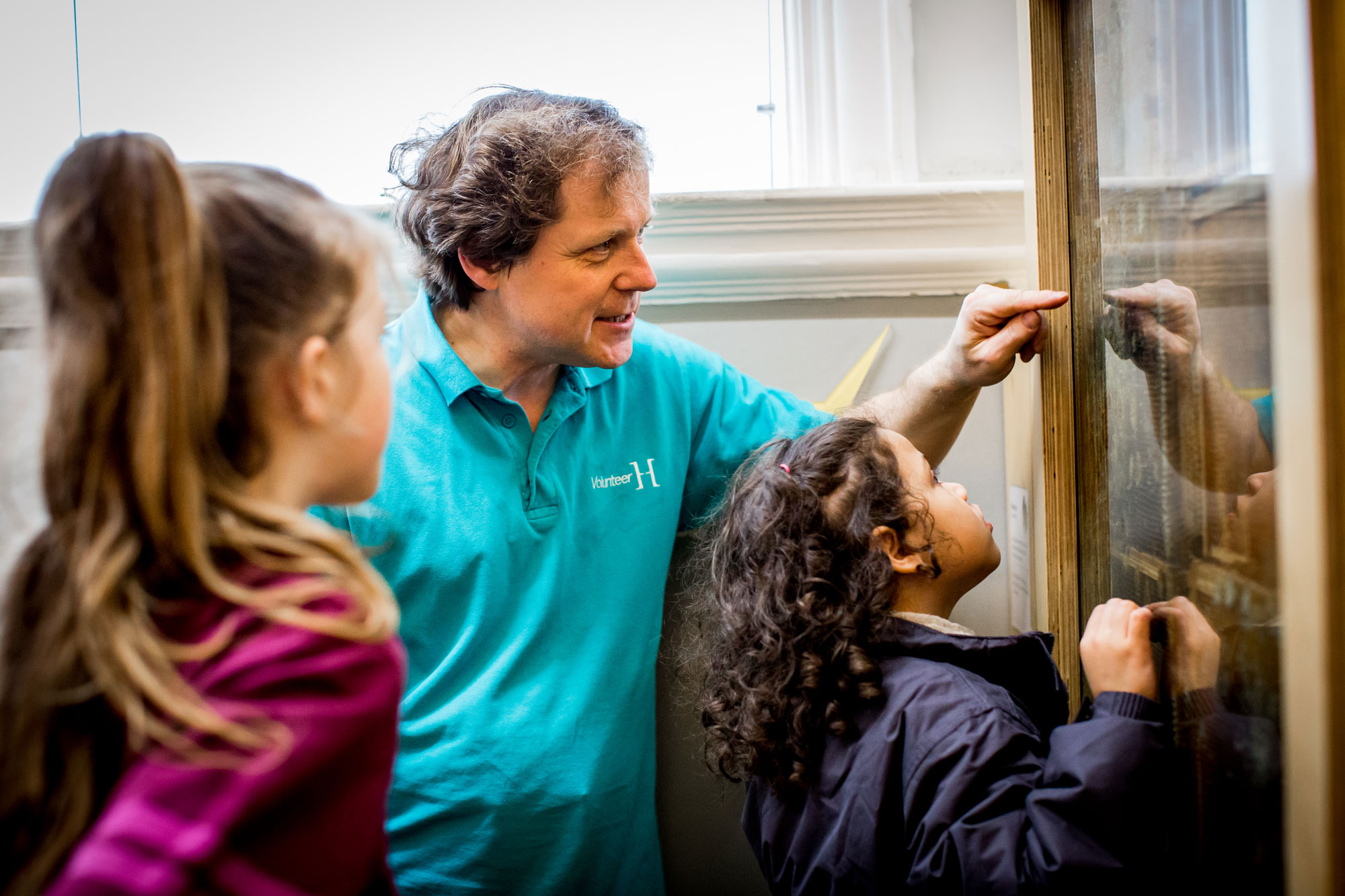 A man in a blue horniman volunteers shirt is showing two girls a see through bee hive