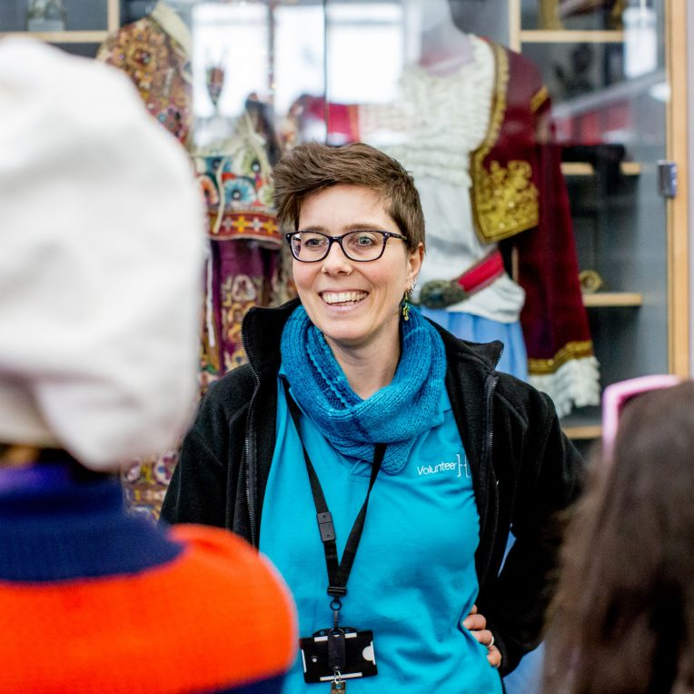 A volunteer in a blue horniman top is smiling at visitors, whose backs we just see in front of the camera. They are standing in a room full of objects