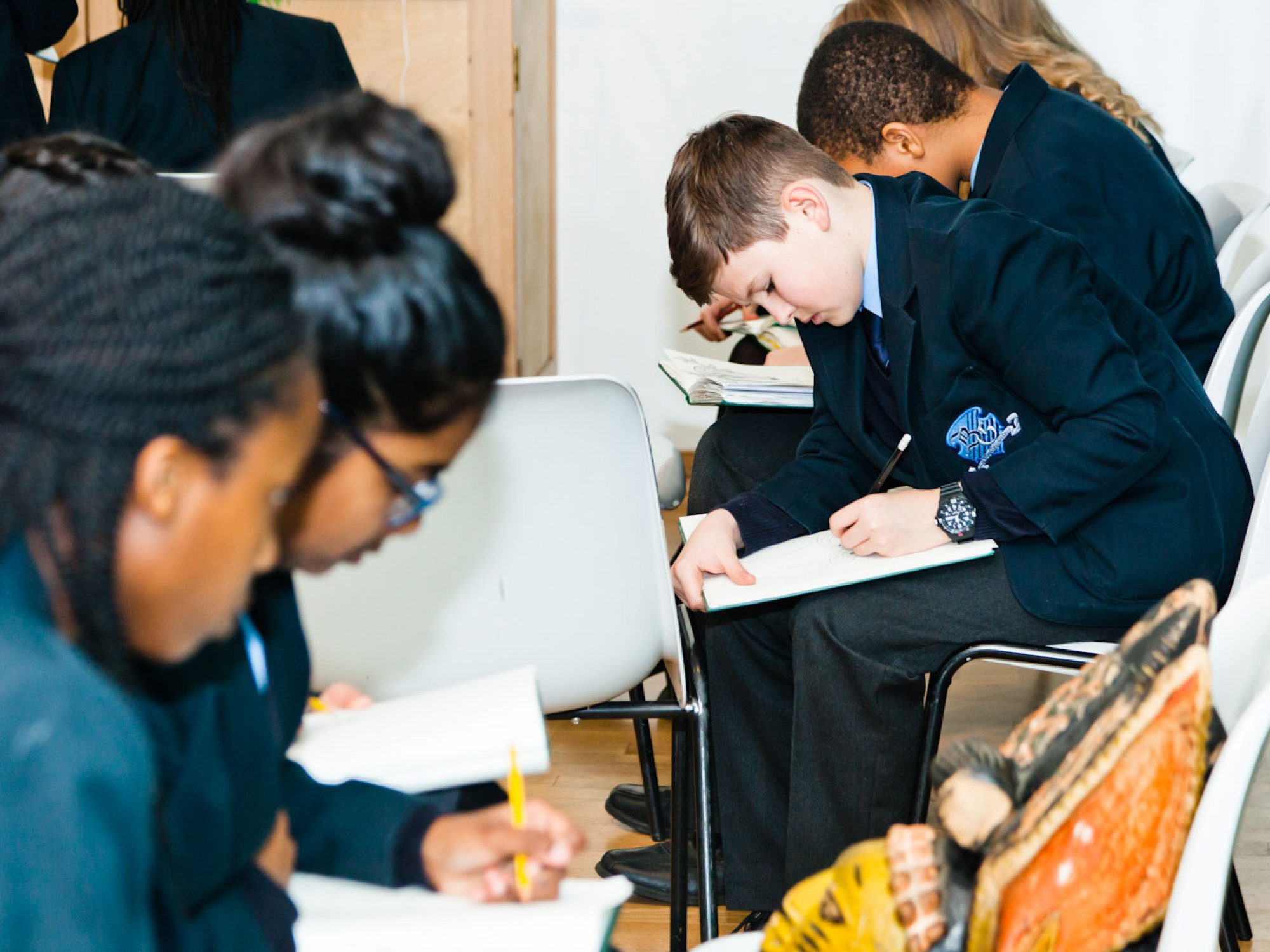A group of school children in blue blazers sat in a room. IN the background are two boys who are drawing something unseen. Close to the camera are two girls who are drawing a mask.