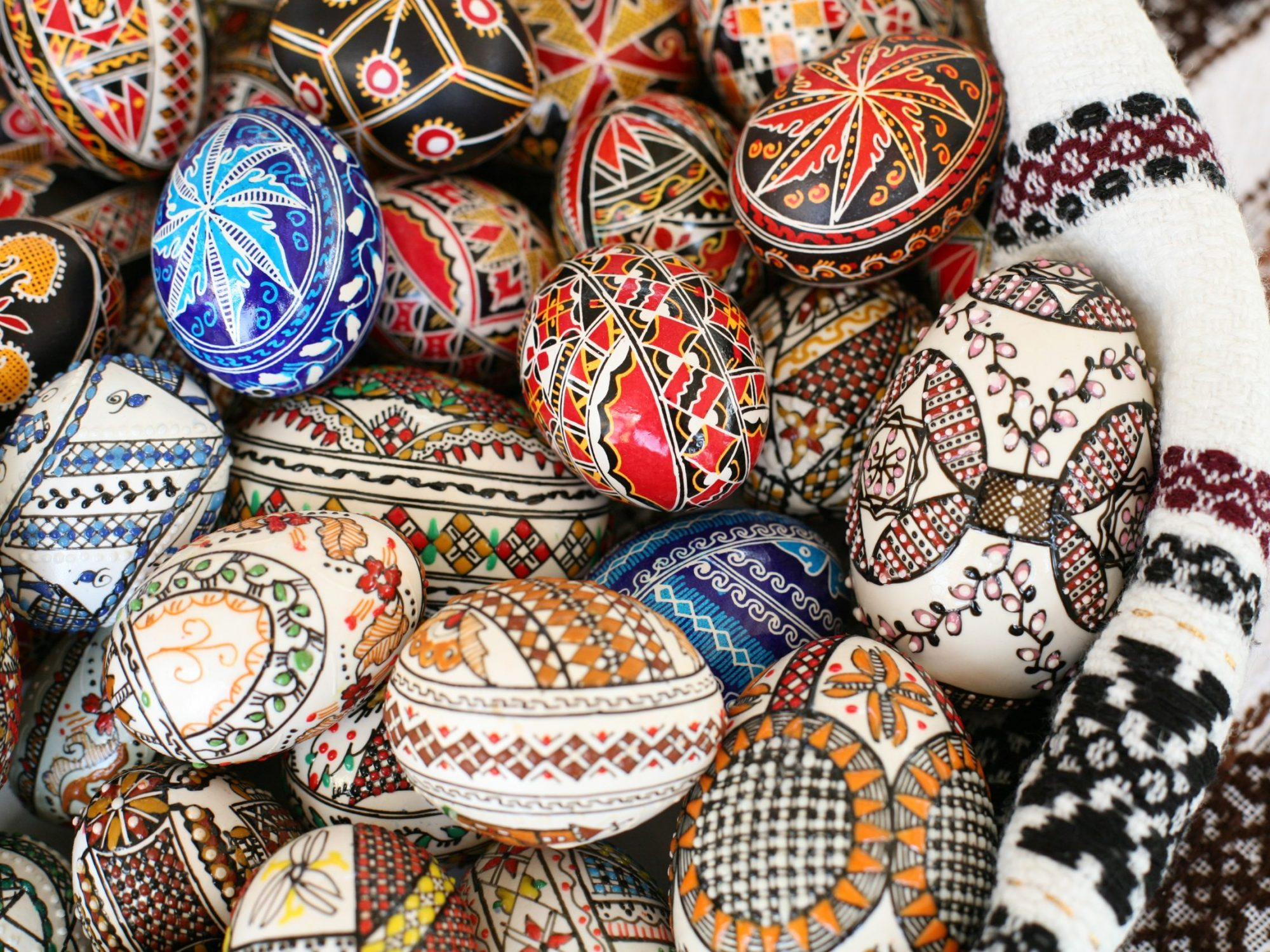 A basket of eggs which are highly decorated in different colours and with different patterns. They are all on a piece of fabric which is also patterned in a similar style