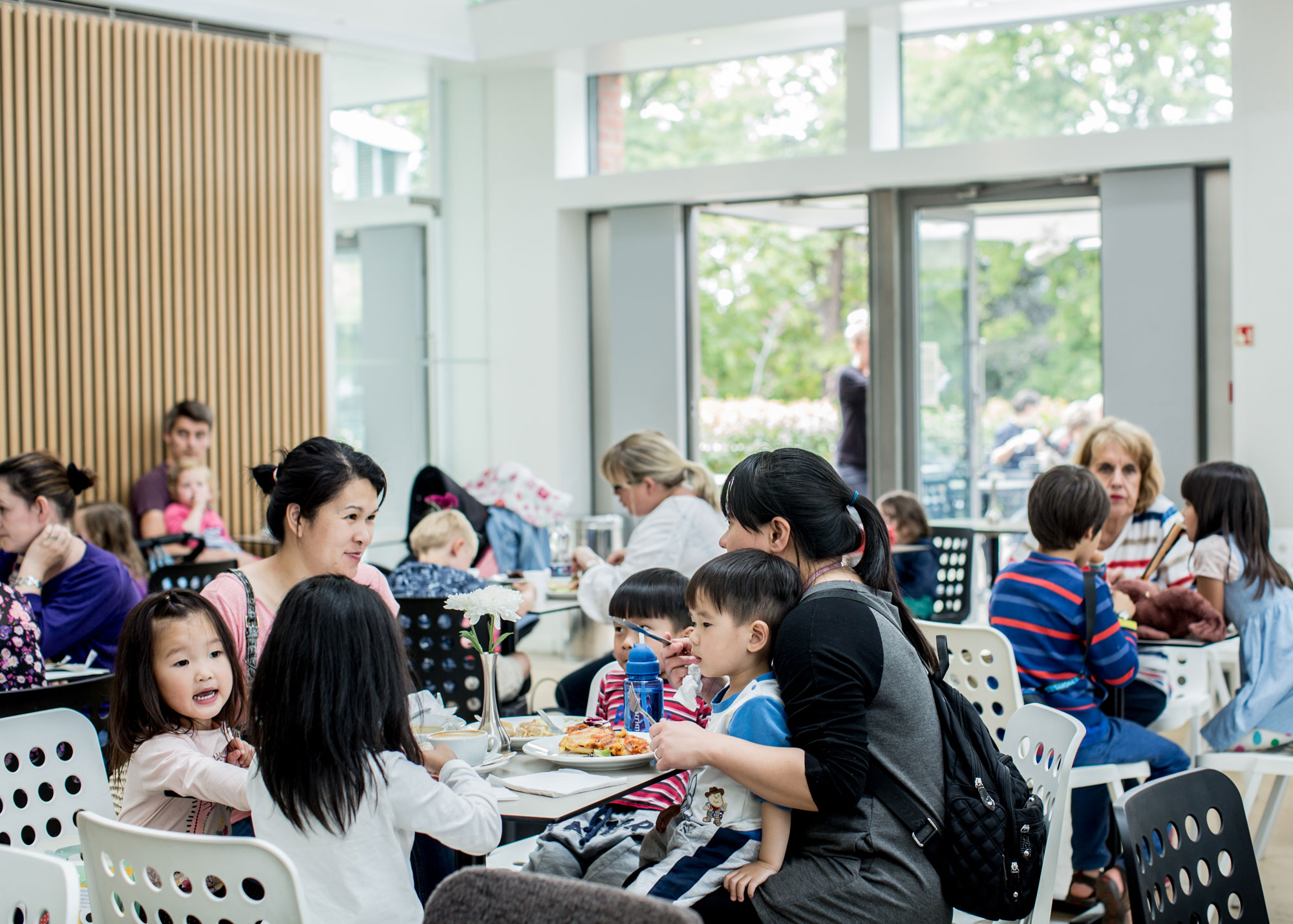 A busy cafe with table and chairs full of adults and children eating. The space is light and airy with glass walls.