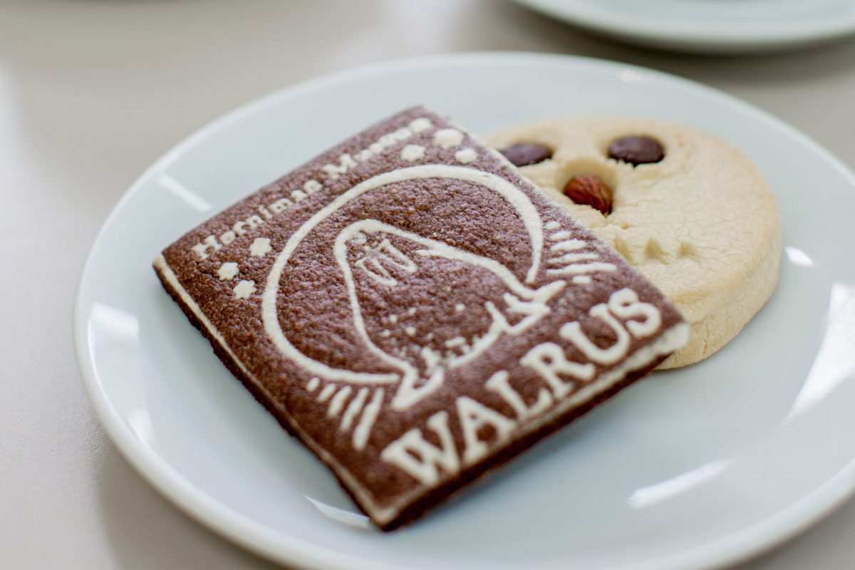 A plate with two biscuits next to two coffees in white china cups. One biscuit is shaped like an owl and the otehr had a picture of a walrus and the word walrus on it.