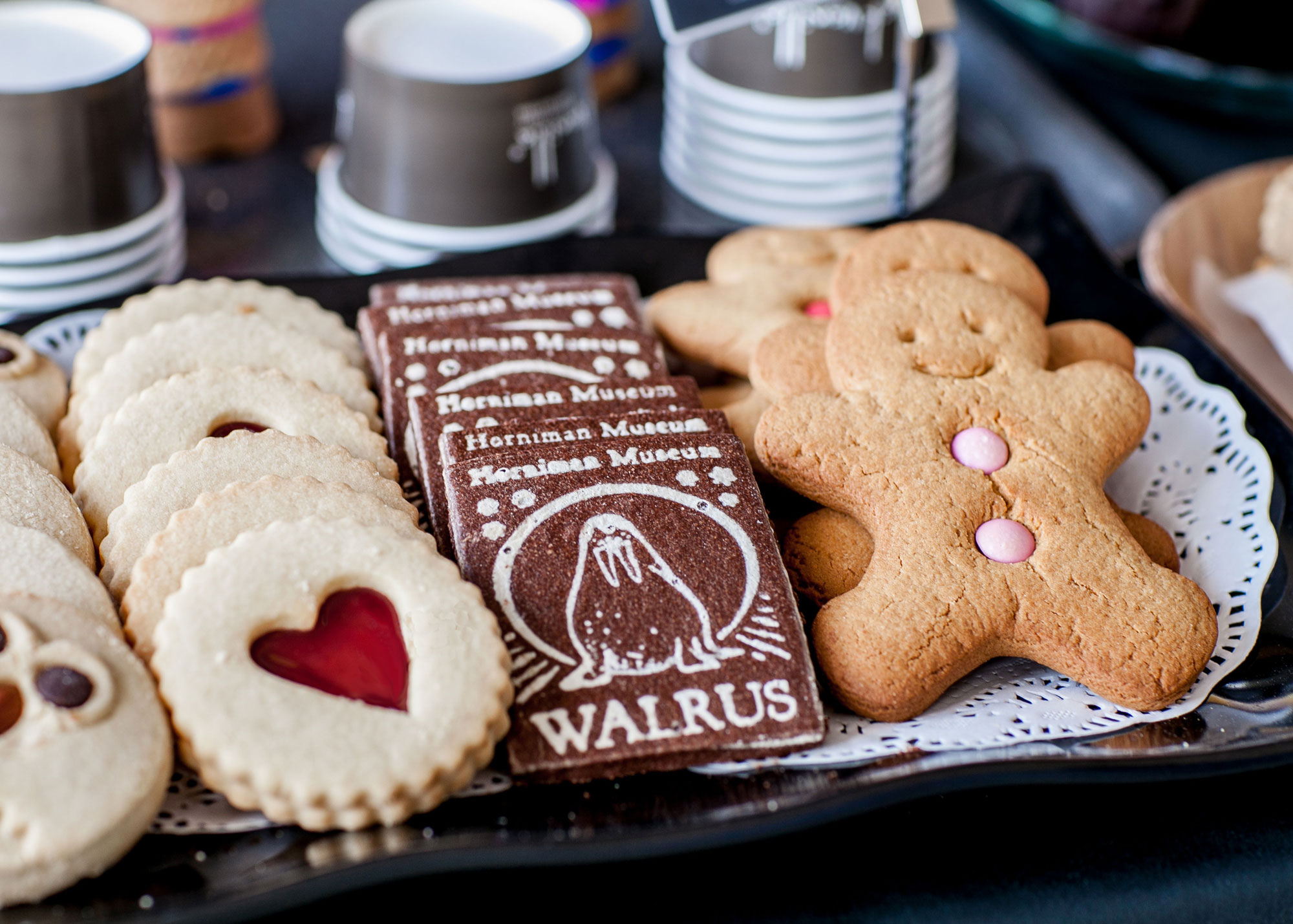 A display of biscuits on a counter. From left to right, a round biscuit with a heart made of jam at the centre, a square chocolate biscuit with a walrus on it and a gingerbread man biscuit with smartie buttons