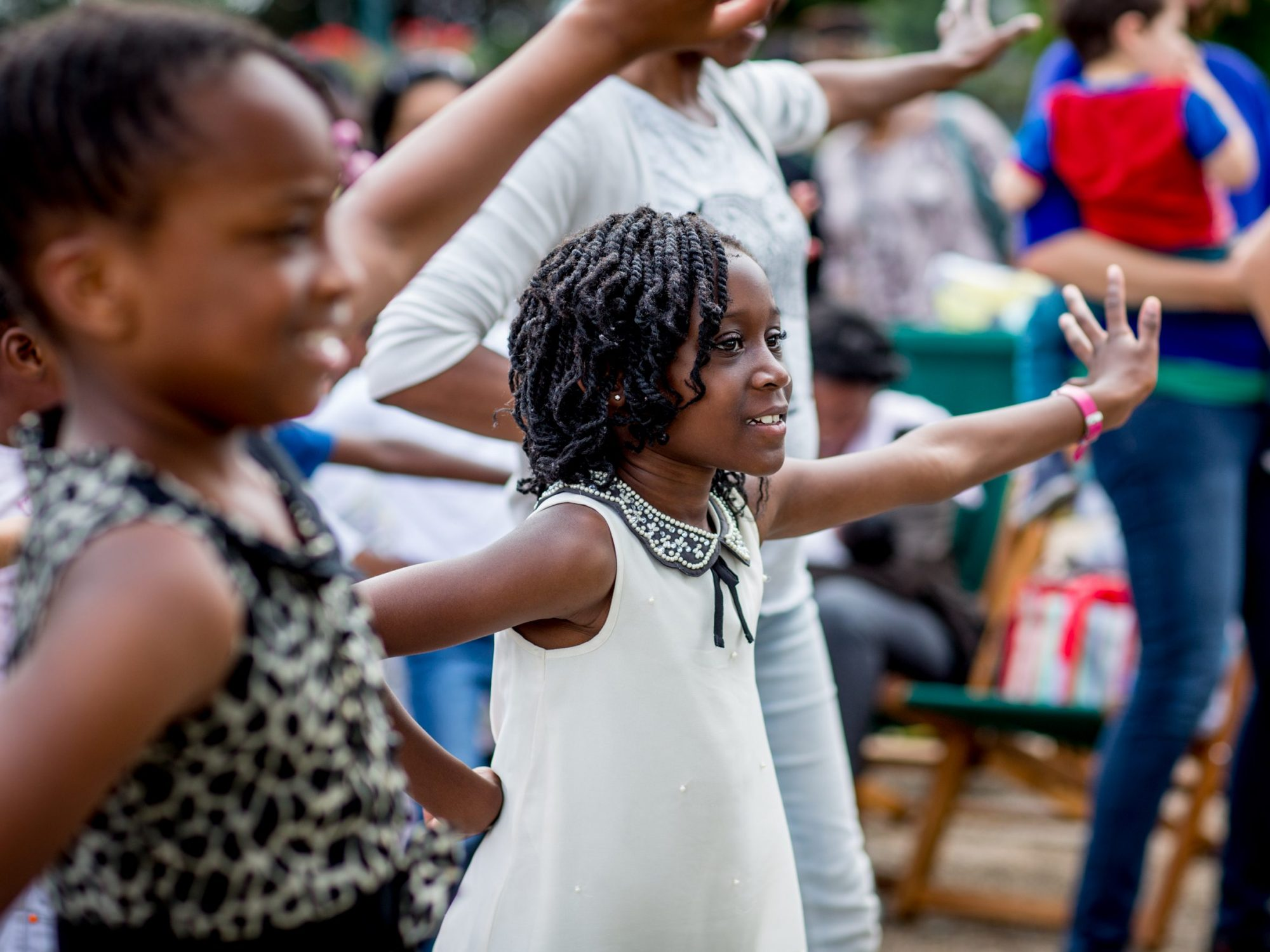 Two girls in close up, in the middle of doing a dance pose, in among other adults and children dancing - they are smiling and their arms are in the air