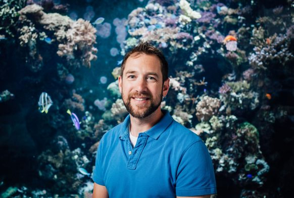 A man in a blue top is seen from the chest up in front of a large aquarium stank with small fishes and corals in it