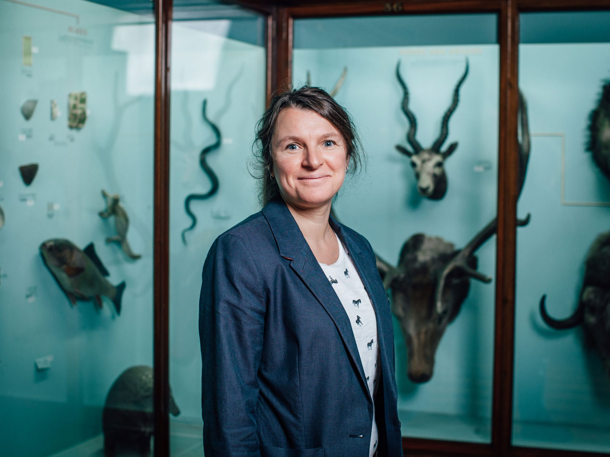 A woman seen from the waist up is wearing a blue jacket and is smiling. She is stood in front of some blue museum cases with taxidermy animals in them like fish, deer and antelope