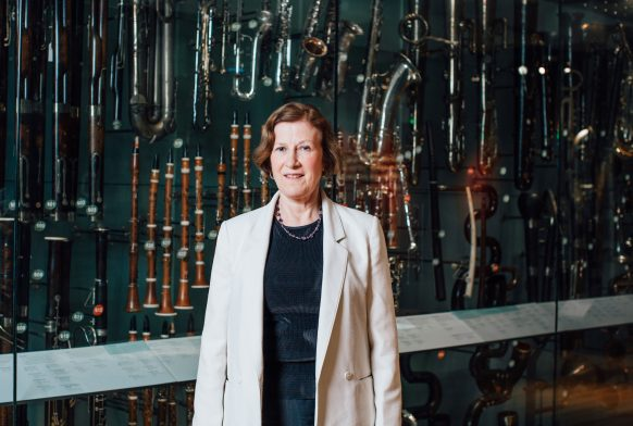 A woman in a white jacket is standing in front of a case with many recorders and other wind instruments on display in it