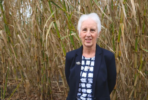 A woman is seen from the waist up wearing a dark blue jacket. She is smiling and stood in front of some bamboo outside.