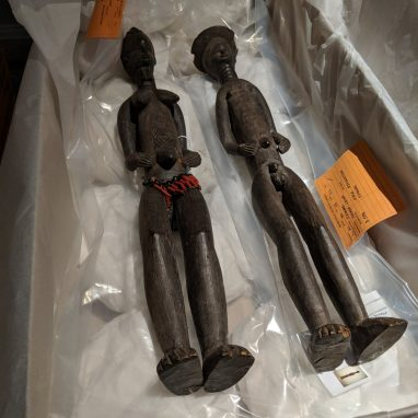 Two wooden figures - a man and a woman - lying in a cardboard box with tissue. The man is wearing a hat and the woman has a beaded apron on