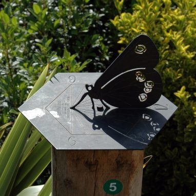 A sundial in the shape of a Butterfly, sat in amongst some shrubbery