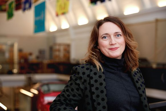 A woman is seen from mid torso up. She is wearing a black spotted jacket and is smiling. Behind her is a gallery which is blurred.