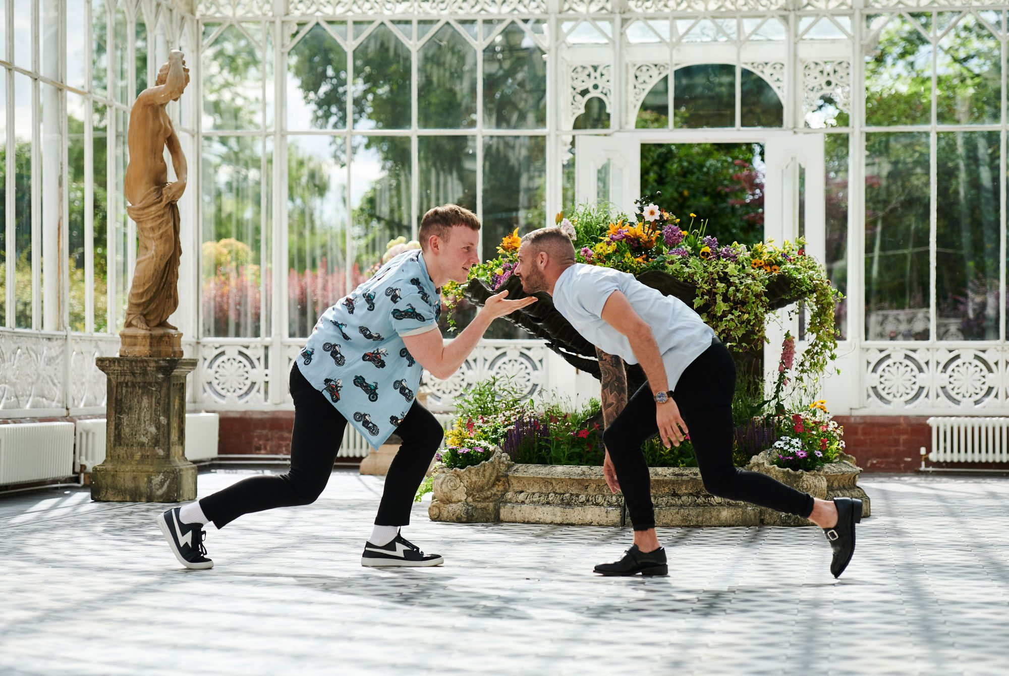 Two men are dancing towards each other in a glass and metal conservatory which has a stone figure and some flowers behind them. They are both wearing jeans and skirts, and are smiling