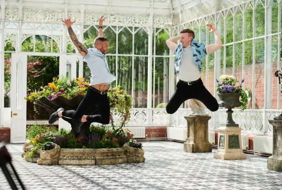 Two men jump high in the air with legs bent and arms stretched up, they are in a glass and white metal conservatory with flowers in the background