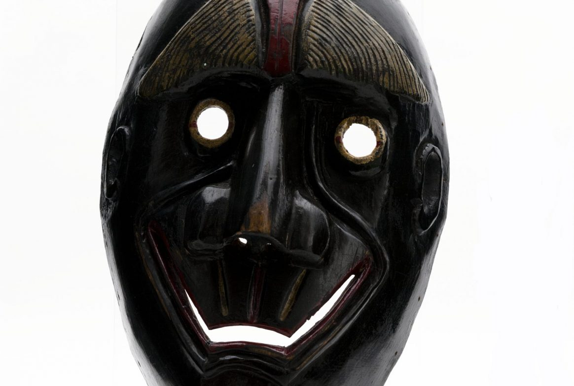 black mask, oval shaped with horns at the top. There are small round holes for the eyes and an opening for the mouth in a wide smile