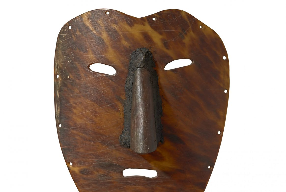 A simple brown flat mask, made from shell, so has a mottled brown colour. There are rivets around the edge, holes cut for two eyes and a small open mouth, with a large node protruding from the face.