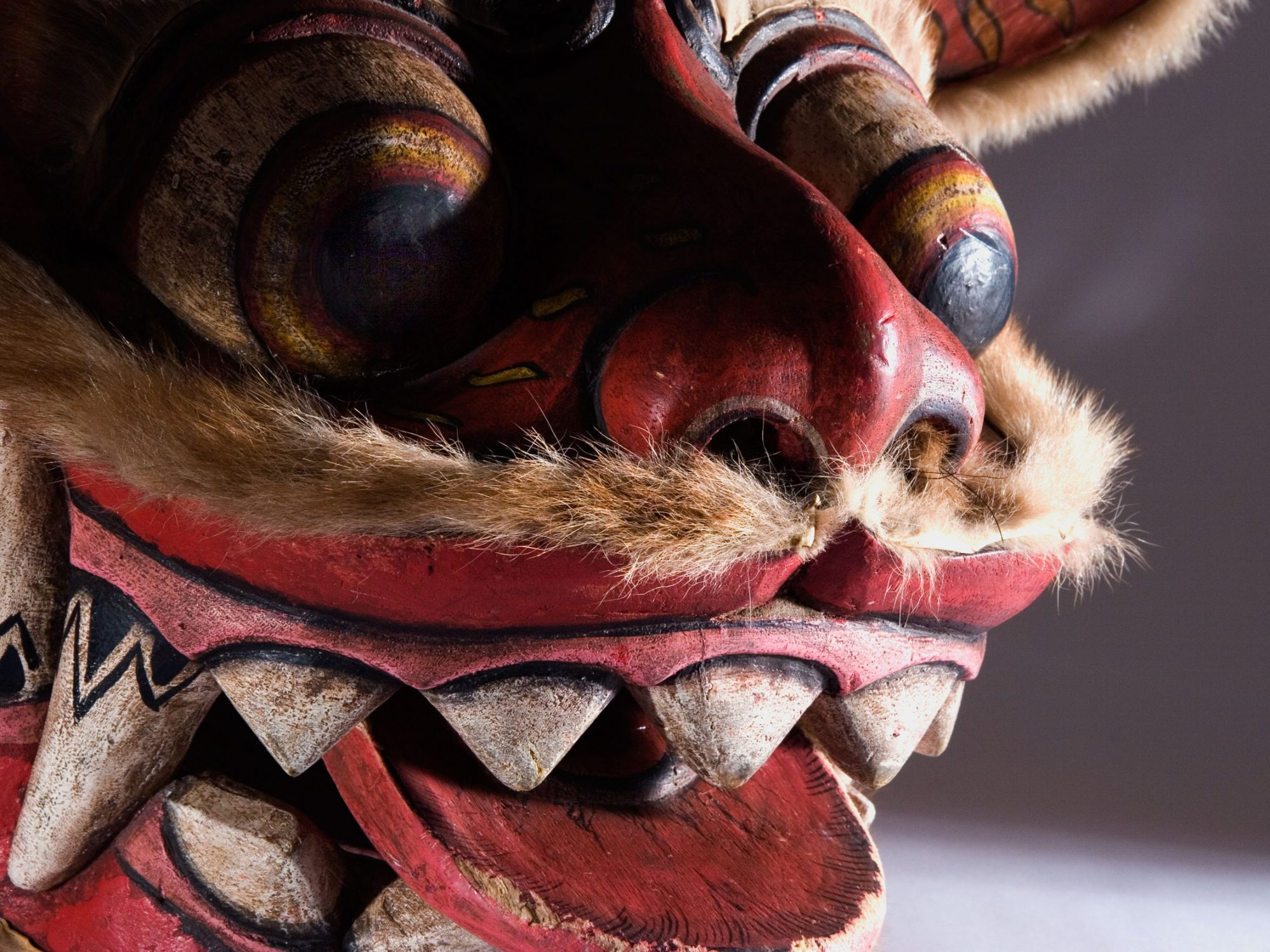 A close up of a Chinese dragon mask face with an open mouth and tongue sticking out