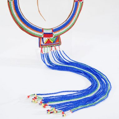 A beaded neck piece made up of blue white red yellow and green coloured beads. There is a wide circular piece off of which a longer strand of beaded fronds hang, which are mainly blue