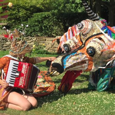 A person is kneeling on the grass playing an accordion in front of a papermache animal that looks like a large colourful dragon