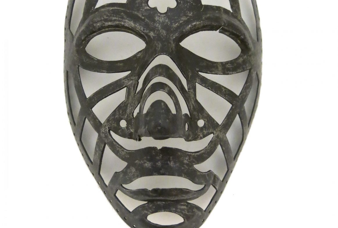 Metal mask, which looks like a decorative frame. Much of the mask is empty space with a metal edge around the eyes, nose , mouth and chin, with empty patches all over between the metal struts. There is a flower cut out at the top above the eyes.