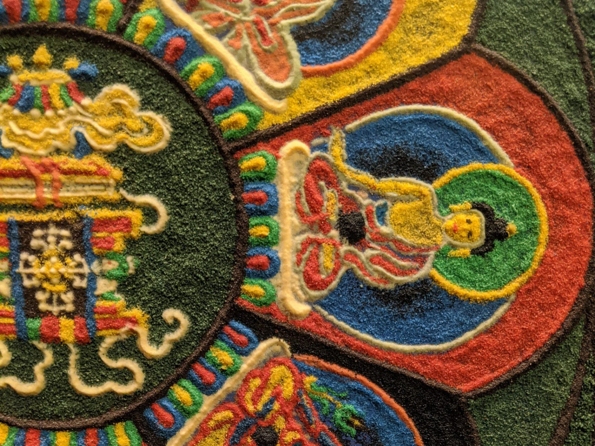 A close up of a picture made of sand. It looks like petals around a central pattern, with small figures of buddha sat in each petal.