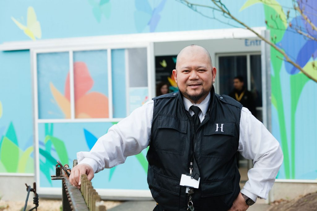 A man stands in fronty of a blue buildings with butterflies on it. He is leaning on a post, and is wearing a black security vest and is smiling