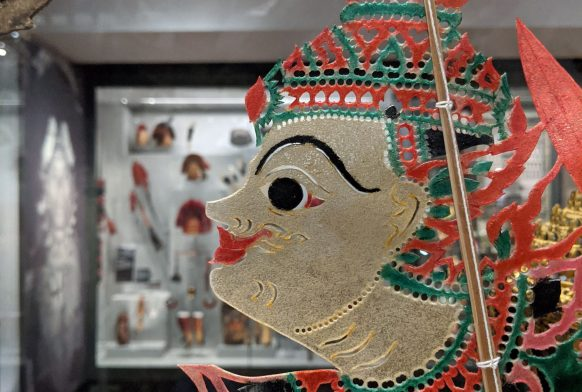 A shadow puppet made of very thin paper, as seen through a glass case. the puppet is wearing an ornate red outfit and we see only the face but it is hard to tell whether they are male or female
