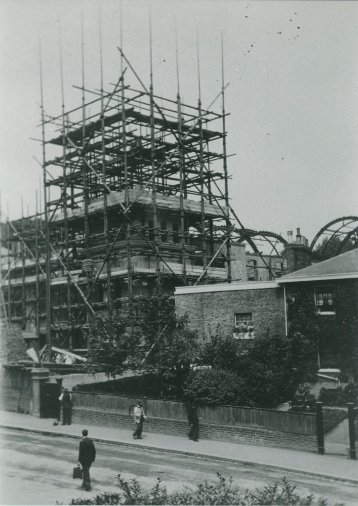A black and white photograph sowing a building with scaffolding around it under construction