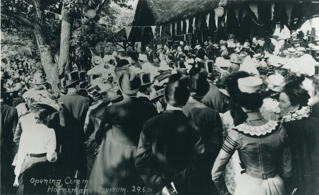 black and white photograph of men and women in stylish Edwardian dress, like top hats and gowns. They are outside in a Garden