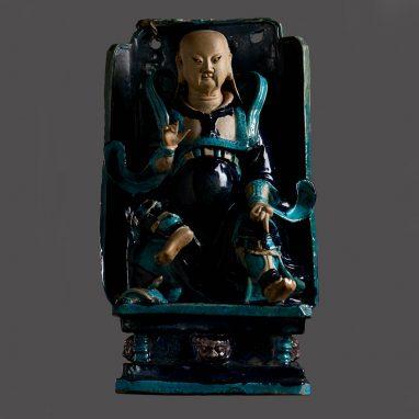 Figure of man sitting in black throne against grey background