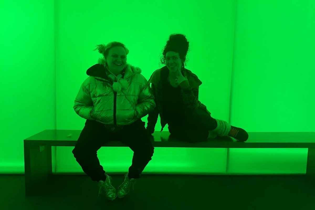 Two female teenagers sitting on bench in green lit room