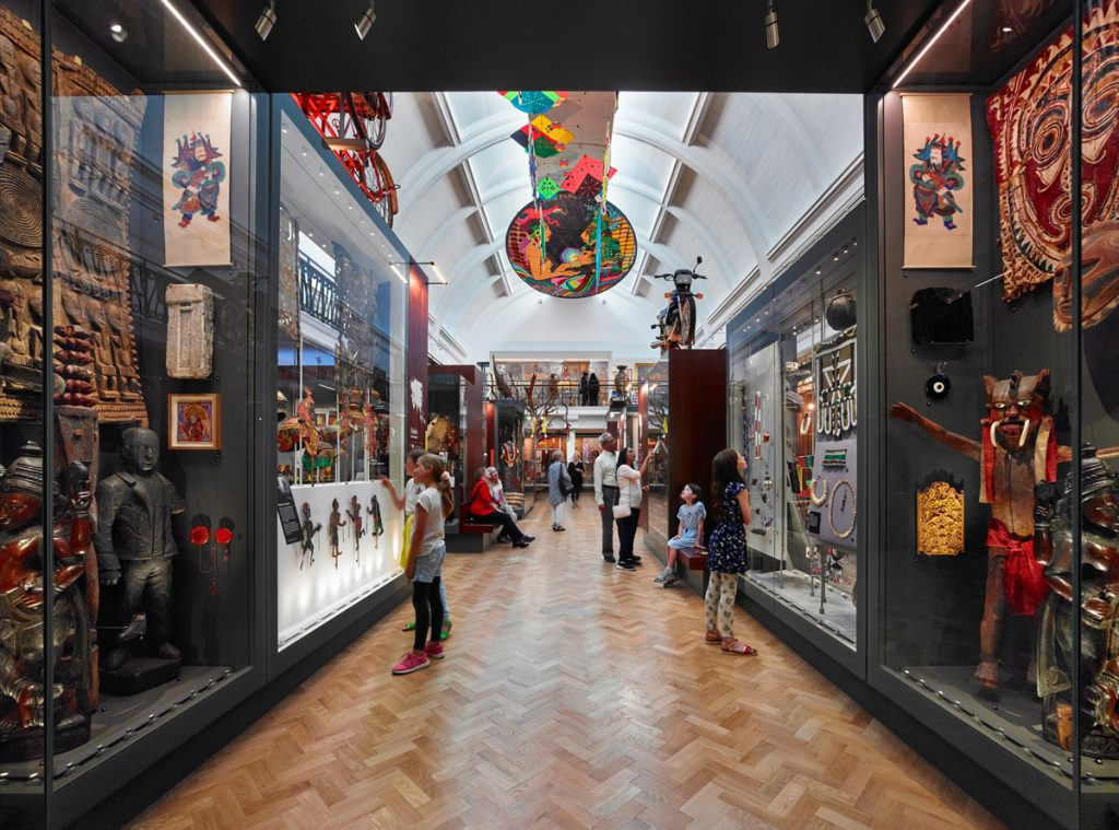 A corridor in a gallery with people looking into cases. There are kites on the ceiling
