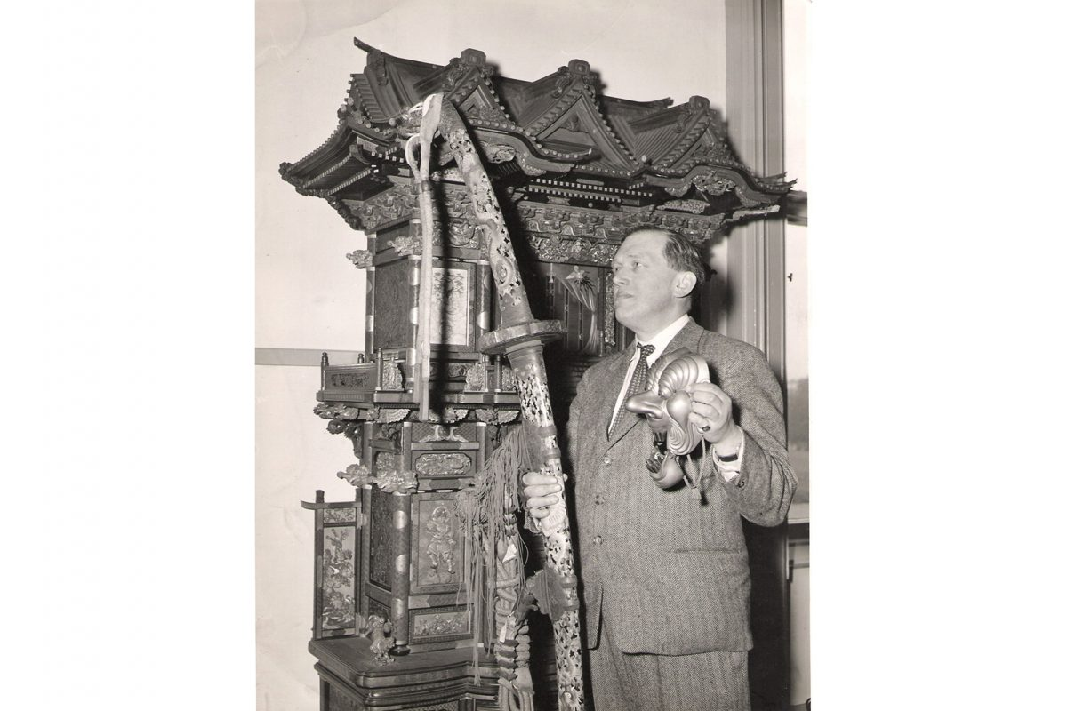 Man standing with sword and other Japanese objects