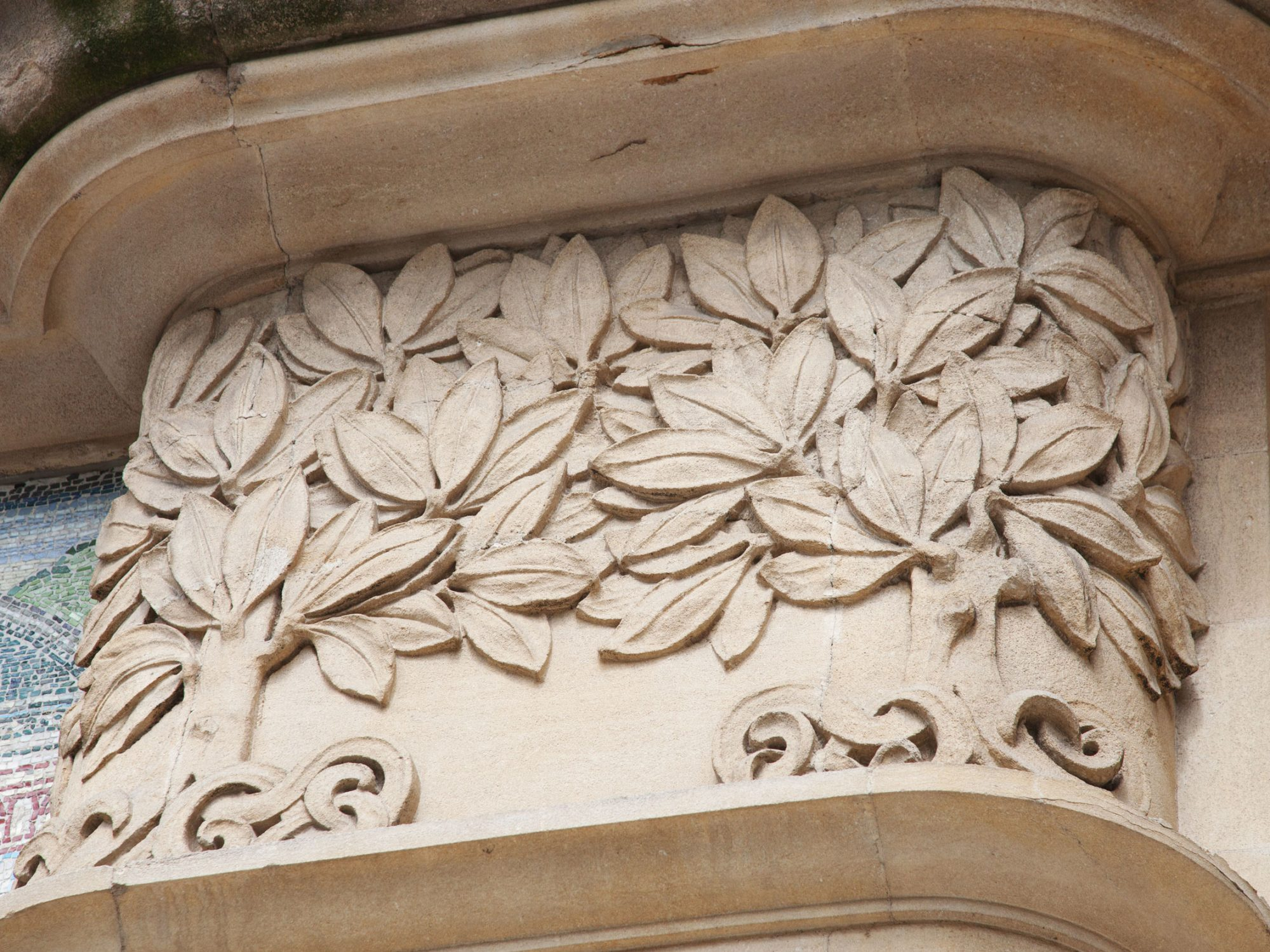 A close up of some trees carved onto the stone facade of the Horniman building