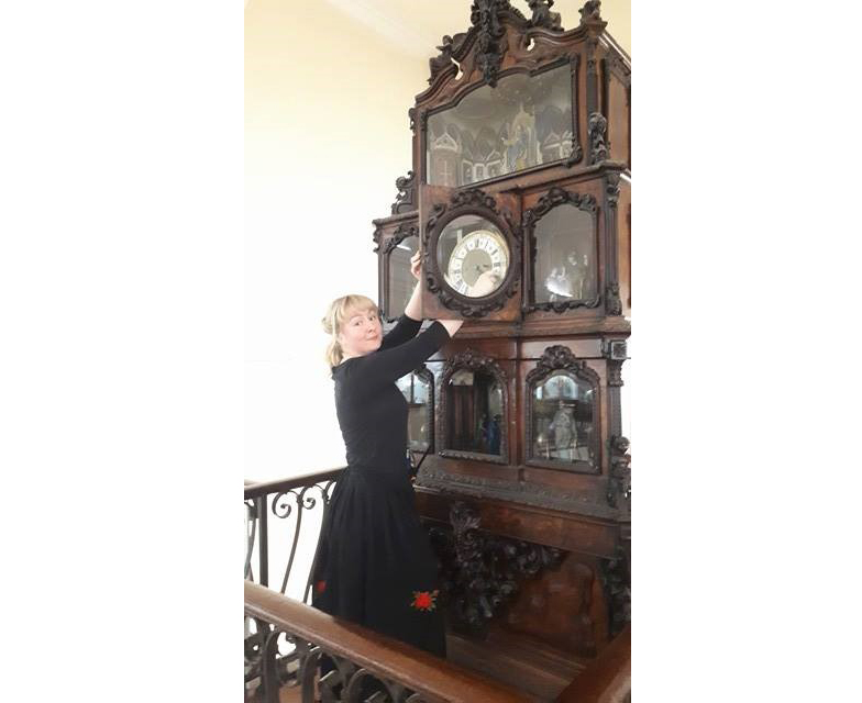 Female visitor host standing next to large clock