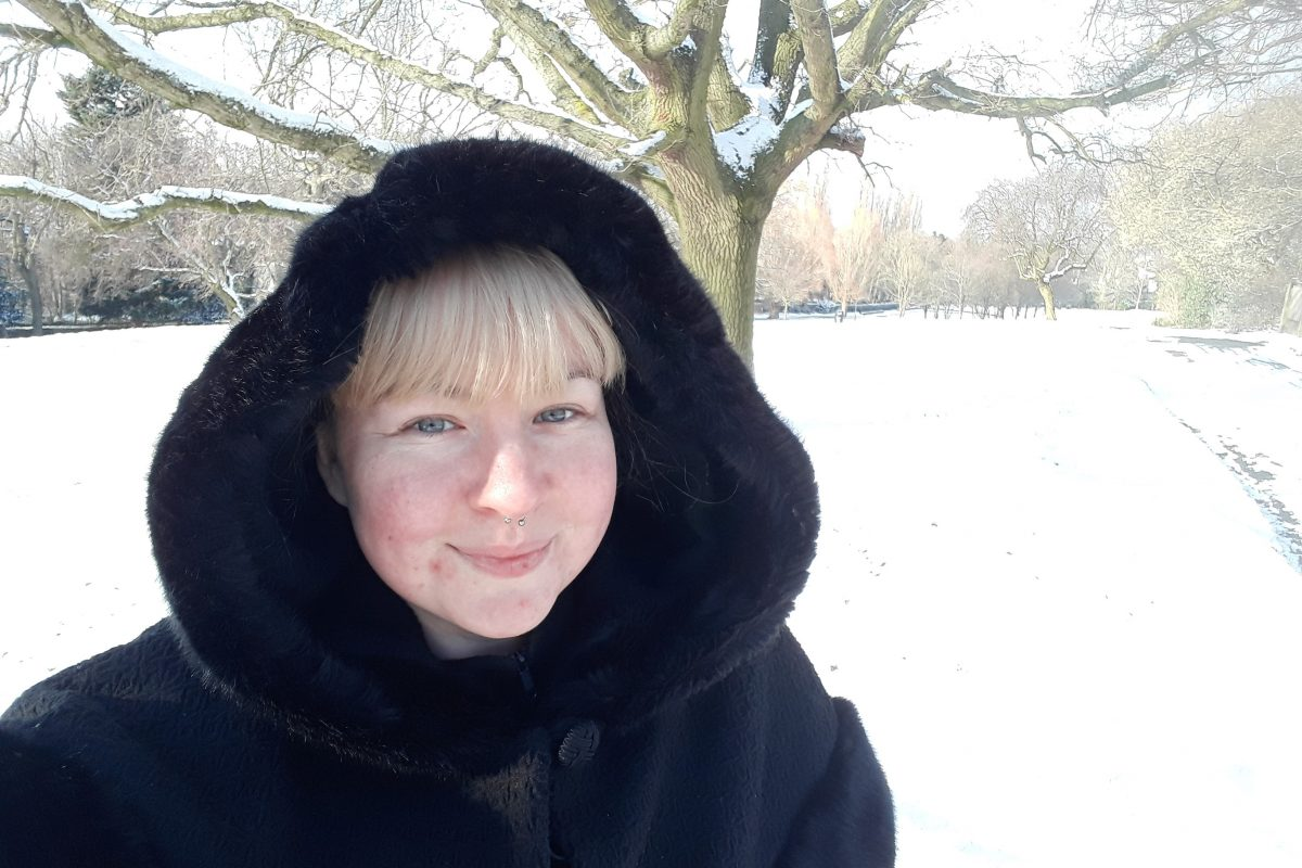 Female in black fax fur coat standing gardens filled with snow.