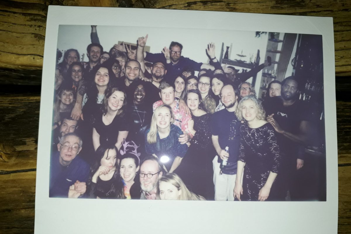 A Polaroid with a large group of men and women gathered together smiling