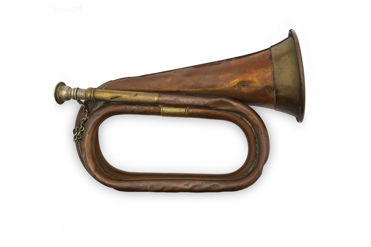 Wind instrument shaped like a curved horn, made from brass. The instrument is on a white background
